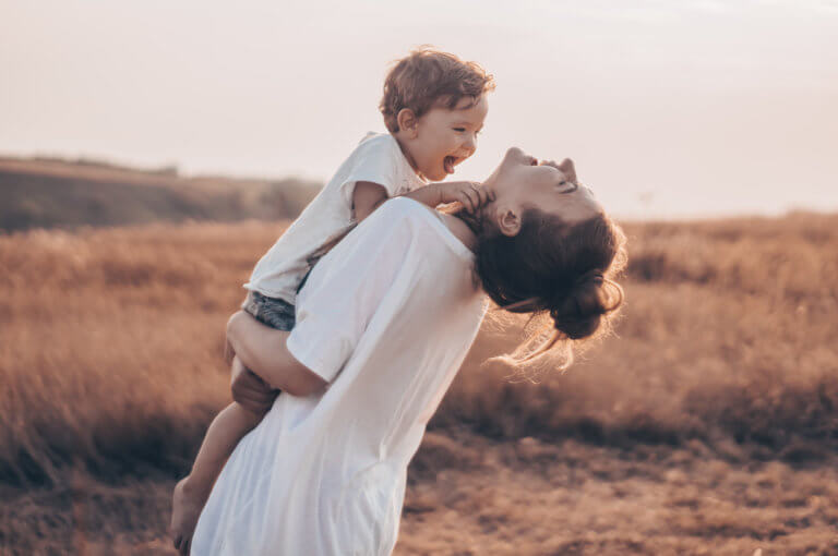 Woman holding young boy and smiling